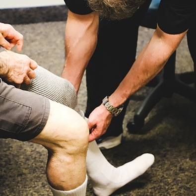Doctor placing compression sock