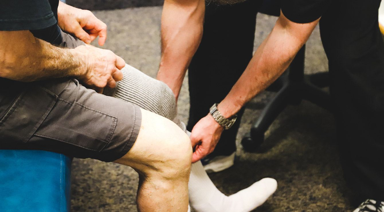 Doctor placing compression device on leg