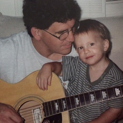 Dr. Tortland playing guitar with one of his children