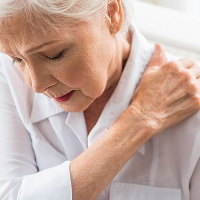 Older woman in pain holding her shoulder
