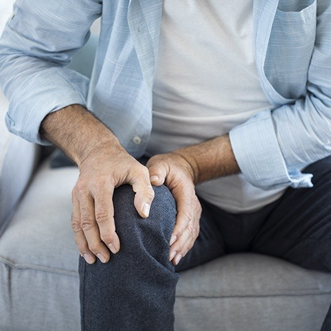 Person in pain holding knee