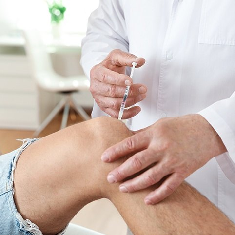 Doctor administering injection in knee