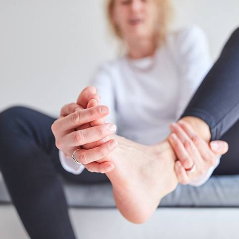 Person holding foot in pain