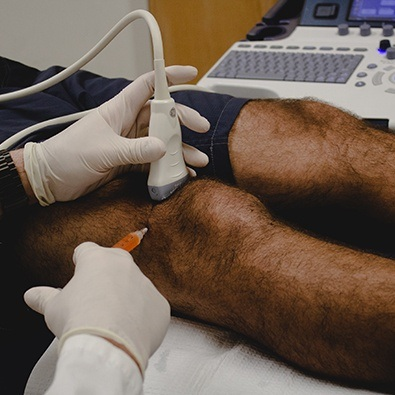 Doctor administering injecting in patient's knee