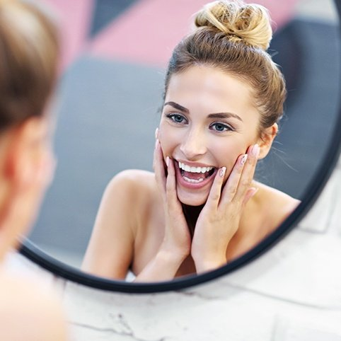 Woman examining smooth skin in mirror