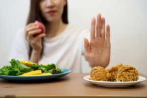 woman with osteoarthritis rejecting fried chicken