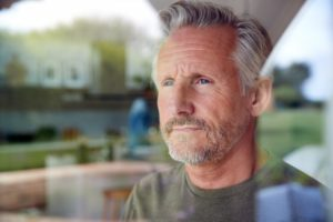 man looking out window worried about osteoarthritis