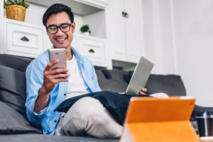 man looking at phone while working at home