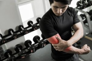 man holding arm due to muscle tear